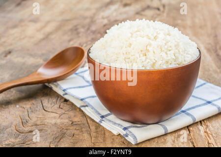 Gekochten Reis in Schüssel mit Geschirrtuch und Löffel auf alten Holztisch - Stockfoto
