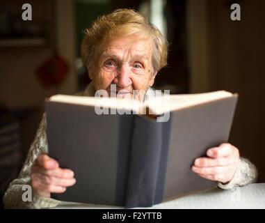 Ältere Dame sitzt und liest dickes Buch auf dem Tisch im Haus. - Stockfoto