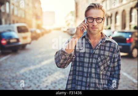 Closeup Portrait des jungen Mannes auf sein Handy in der Stadt sprechen - Stockfoto
