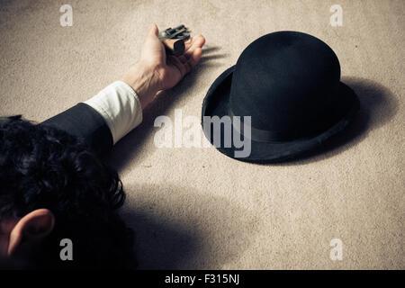 Ein Mann liegt tot auf dem Boden mit seinen Hut und seinen revolver - Stockfoto