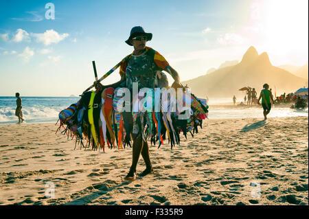 RIO DE JANEIRO, Brasilien - 20. Januar 2013: Anbieter verkaufen Bikini Badeanzüge Spaziergänge am Strand von Ipanema in einen nebligen Sonnenuntergang. Stockfoto