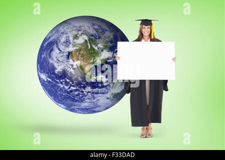 Zusammengesetztes Bild voller Länge einer Frau mit einem leeren Blatt vor ihr wie sie lächelt - Stockfoto
