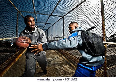 Zwei junge Männer zu Fuß hinunter eine Fußgängerbrücke mit einem Basketball zu spielen. Stockfoto
