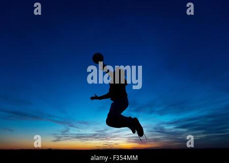 Silhouette eines jungen spielen im Freien in der Abenddämmerung - Stockfoto