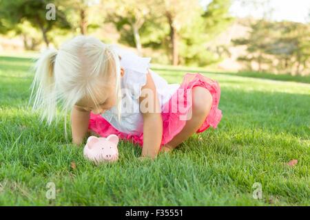 Niedliche kleine Mädchen Spaß mit ihr Sparschwein draußen auf dem Rasen. - Stockfoto