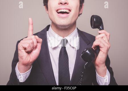 Junger Geschäftsmann auf dem Handy bekommt eine glänzende Idee - Stockfoto