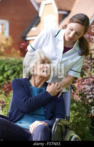 Pflegeperson Senior Frau im Rollstuhl schieben - Stockfoto
