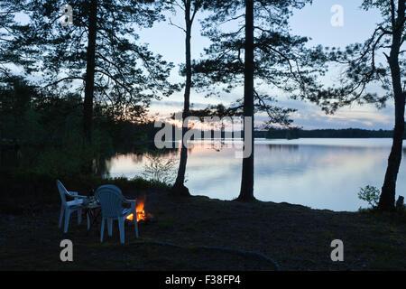 DACKESKOGEN, SCHWEDEN AM 13. MAI 2012. Blick auf die nordische Nacht mit Nordic Light an einem See. Lagerfeuer und - Stockfoto