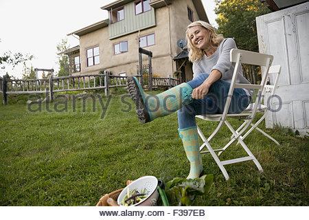 Lächelnde Frau anziehen Gummistiefel im Garten - Stockfoto