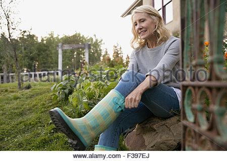 Frau auf karierten Gummistiefel im Garten - Stockfoto
