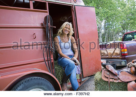 Lächelnde Frau Porträt in Tür Pferdeanhänger - Stockfoto