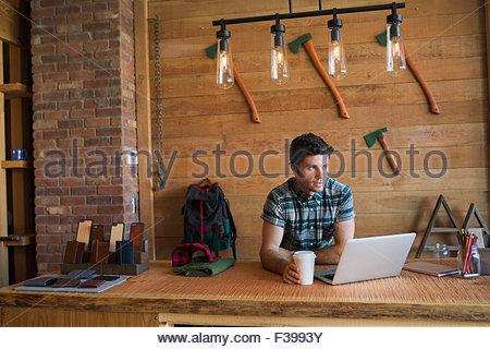 Geschäftsinhaber Kaffeetrinken am Laptop Ladentheke - Stockfoto