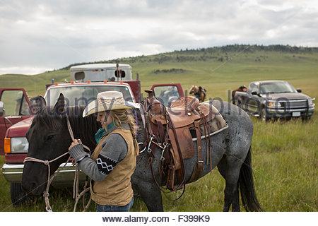 Weibliche Rancher mit Pferd in der Nähe von LKW im Feld - Stockfoto
