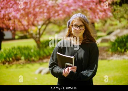 Junger Student stehend mit Bücher in der hand - Stockfoto