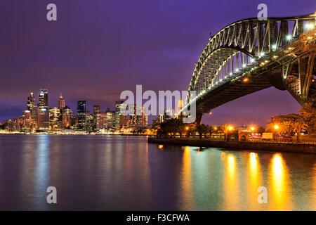 Sydney CBD Cityline von beleuchteten Hochhäuser und die Harbour Bridge mit bunten Reflexion in den unscharfen Hafen - Stockfoto