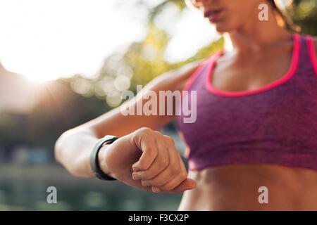 Junge Fitness Frau betrachten ihre Smartwatch während der Einnahme einer Pause von Sporttraining. Sportlerin, die - Stockfoto