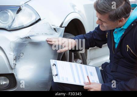 Automechaniker Workshop Inspektion Schäden an Fahrzeug und Reparatur Kostenvoranschlag ausfüllen - Stockfoto
