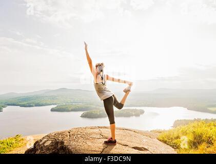 Seitenansicht der jungen Frau, die Ausübung auf Berggipfel - Stockfoto