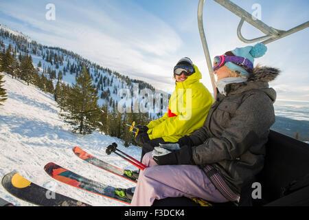 Paar in Skibekleidung sitzen am Skilift - Stockfoto