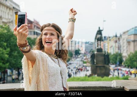 Glückliche junge Brünette böhmischen Frau Tourist machen Selfie im historischen Zentrum von Prag. Im Hintergrund - Stockfoto