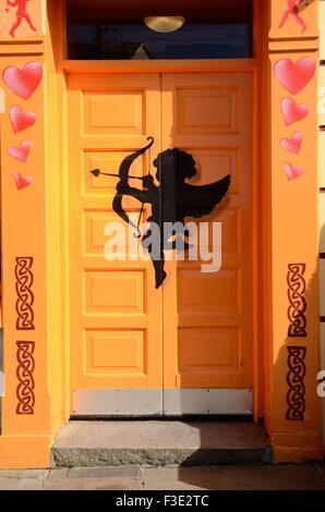 Amor auf einem hellen orange Tür of The Matchmaker Bar Lisdoonvarna County Clare Ireland - Stockfoto