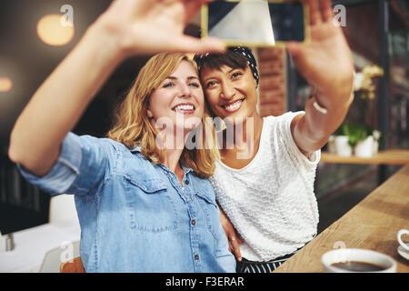 Lächelnd attraktive Freundinnen nimmt man eine Selfie zusammen, wie sie in der Cafeteria genießen Sie eine Tasse - Stockfoto
