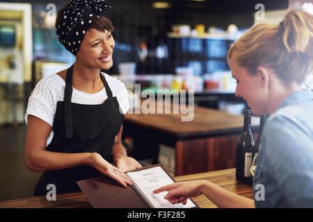 Kunden, die Überprüfung einer Weinkarte in einem Pub präsentiert ihr durch eine attraktive freundliche junge afrikanische - Stockfoto