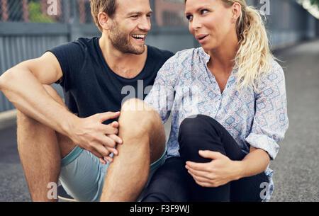 Paare, die haben einer guten Zeit beim Sitzen auf dem Boden - Stockfoto