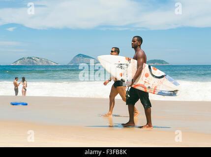 RIO DE JANEIRO, Brasilien - 20. Februar 2014: Paar junge brasilianische Surfer mit Surfbrettern Ipanema Strand entlang - Stockfoto