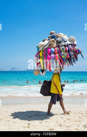 RIO DE JANEIRO, Brasilien - 22. Januar 2014: Strand Verkäufer verkaufen Bikinis und Hüte trägt seine Ware am Strand - Stockfoto