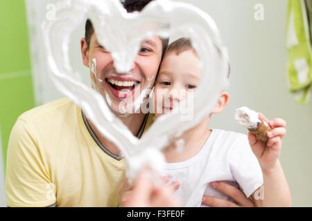 Papa und Kind Sohn Kind zeichnen Herzform auf Spiegel mit Rasierschaum spielen im Bad - Stockfoto