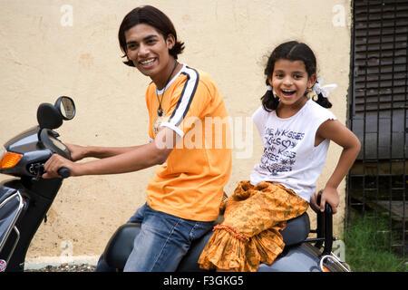 Südasiatische Indianerjunge Kaushik und Mädchen Sanchi Sitzgelegenheiten auf Roller; Bombay Mumbai; Maharashtra; - Stockfoto