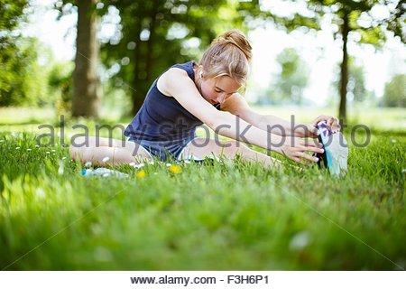 Junges Mädchen im Park erstreckt sich dabei auf Rasen - Stockfoto
