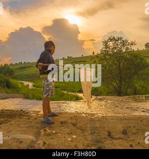 Kleiner Junge Angeln im Bach, mit Angeln net, niedrigen Winkel Ansicht - Stockfoto