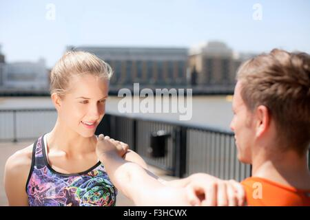 Läufer, die Dehnung am Flussufer, Wapping, London - Stockfoto