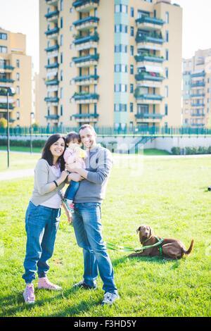 Porträt von Mitte erwachsenes paar mit Kleinkind Tochter und Hund im park - Stockfoto