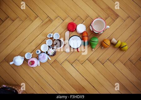 Draufsicht der Cupcakes, Spielzeug und Tassen auf Parkett - Stockfoto