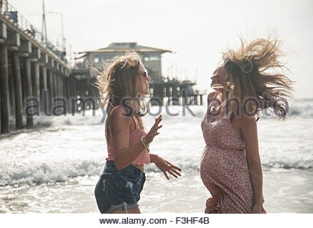 Zwei junge Frauen reden am windigen Beach, Santa Monica, Kalifornien, USA - Stockfoto