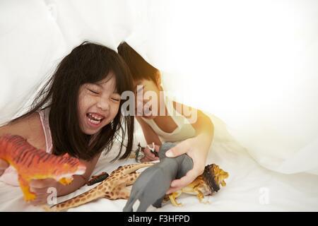 Chinesischen jungen und Mädchen im Bett spielen mit ihren Spielsachen unter der Bettwäsche - Stockfoto