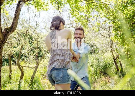 Junges Paar Hand in Hand im Wald lächelnd herumalbern - Stockfoto