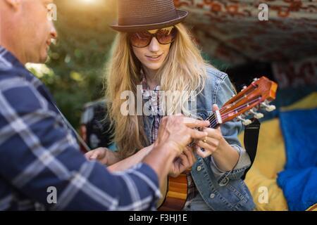 Reifer Mann zeigt Freundin wie Ukulele zu spielen, während camping in der Boot abholen - Stockfoto