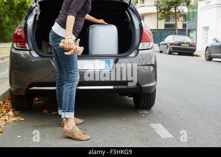 Frau stehend neben dem Auto, indem Koffer in offenen boot - Stockfoto