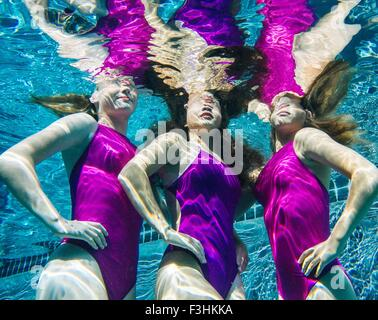 Drei weibliche Schwimmer unter Wasser, Hände auf den Hüften - Stockfoto