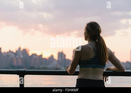 Junge Frau von Geländer stehen, betrachten, Rückansicht - Stockfoto