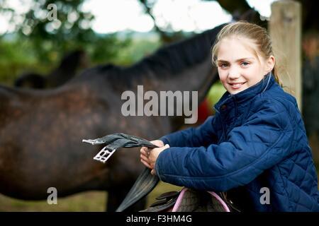Mädchen-Reiterin Vorbereitung Sattel - Stockfoto