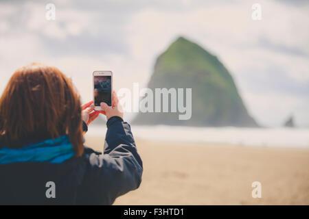 Eine junge Frau nutzt ihr Smartphone, um Haystack Rock in Cannon Beach fotografieren. - Stockfoto