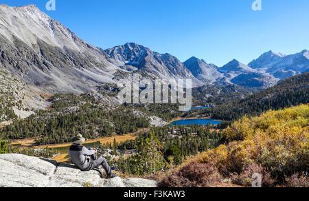 Wanderer am Aussichtspunkt neben der Mono Pass Trail entspannende sieht kleine Seen-Tal im Rock Creek Canyon in - Stockfoto