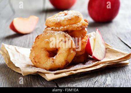Apfelringe auf Backpapier auf rustikalen Tisch