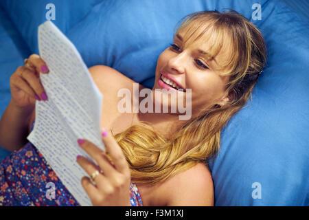 Kaukasische Jugendlicher empfangenden Liebesbrief von ihrem neuen Freund. Das Mädchen legt auf Bett und hält den - Stockfoto
