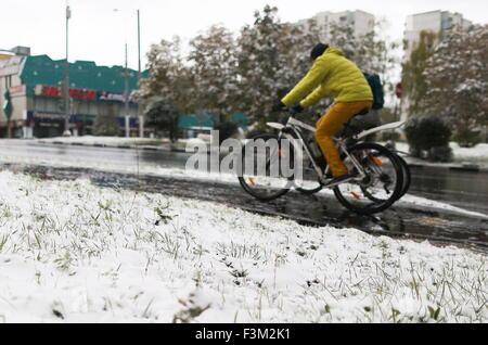 Moskau, Russland. 9. Oktober 2015. Menschen auf Fahrrädern während eines Schneefalls. © Anton Novoderezhkin/TASS/Alamy - Stockfoto